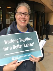 "Photo of Deb Deveno, O.D. smiling holding sign that reads ""Working Together for a Better Kaiser"""